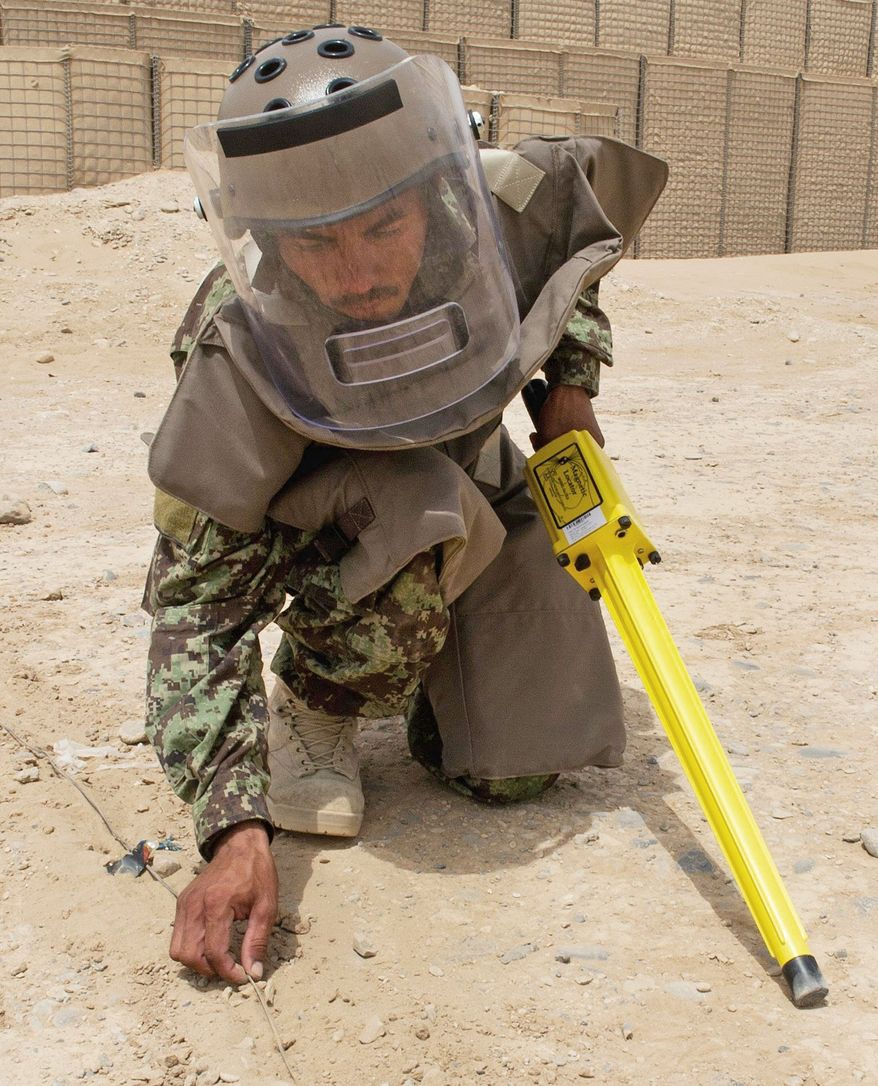 An Afghan soldier practices roadside bomb detection techniques at Camp Dwyer. NATO makes a high priority of sharing its bomb-related expertise with Afghan forces. (Associated Press)