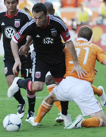 D.C. United's Hamdi Salihi, left, pushes past Houston Dynamo's Andre Hainault (31) during the second half of an MLS soccer match Saturday, May 12, 2012, in Houston. The Dynamo won 1-0. (AP Photo/Pat Sullivan)