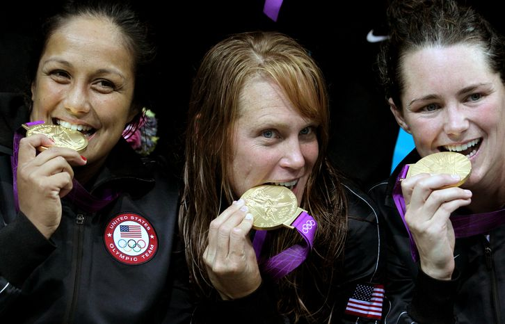 United States' Brenda Villa, from left, Heather Petri and Jessica Steffens bite their gold medals during the women's water polo medal ceremony at the 2012 Summer Olympics, Thursday, Aug. 9, 2012, in London. The U.S. beat Spain 8-5. (AP Photo/Julio Cortez)