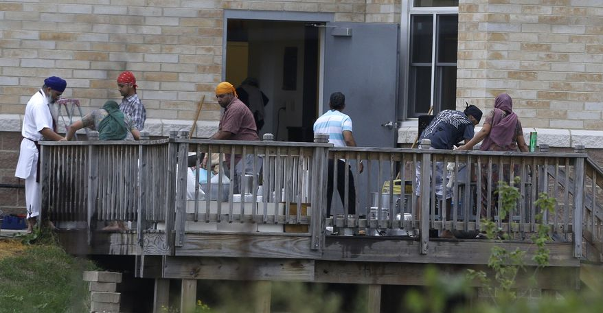 Members of the Sikh temple of Wisconsin in Oak Creek, Wis., wash items Aug. 9, 2012, as they return for the first time since a mass shooting at the temple four days earlier that claimed six members. (Associated Press)