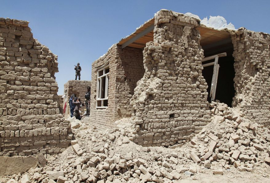 ** FILE ** An Afghan security man stands guard on the roof of a damaged house following a gun battle between militants and Afghan security forces on the outskirts of Kabul, Afghanistan, Thursday, Aug. 2, 2012. (AP Photo/Musadeq Sadeq)
