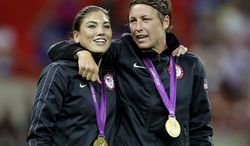 United States' Abby Wambach, right, and teammate Hope Solo celebrate winning the gold medal during in the women's soccer final against Japan at the 2012 Summer Olympics, Thursday, Aug. 9, 2012, in London. (AP Photo/Kirsty Wigglesworth)