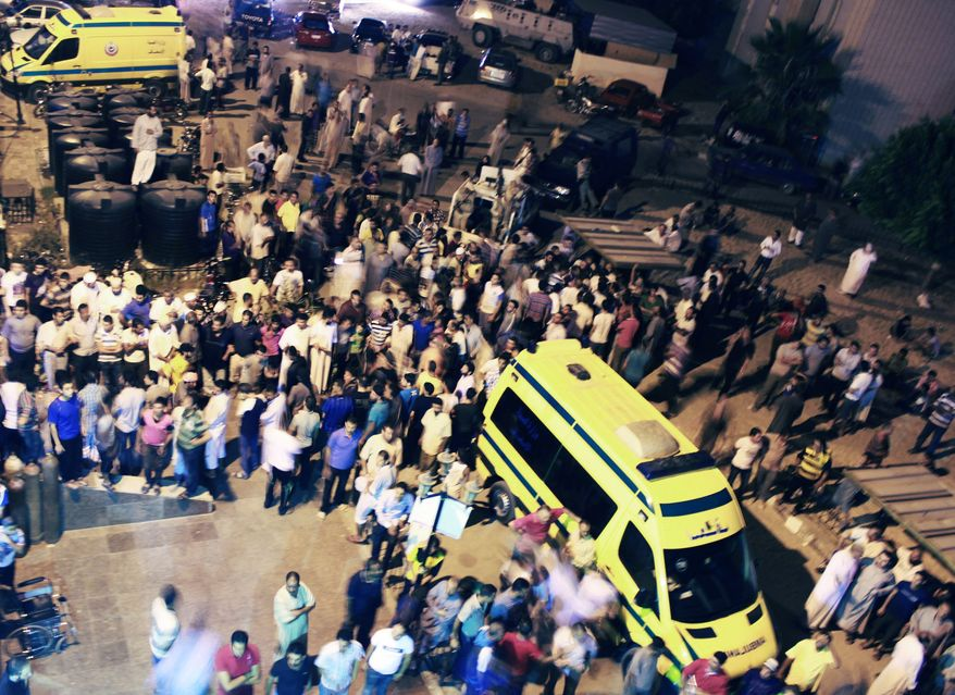 **FILE** Egyptians stand Aug. 5, 2012, outside the El Arish hospital, after an attack which Egypt and Israel blamed on Islamist militants from the Hamas-run Gaza Strip in Egypt's northern Sinai Peninsula. (Associated Press)