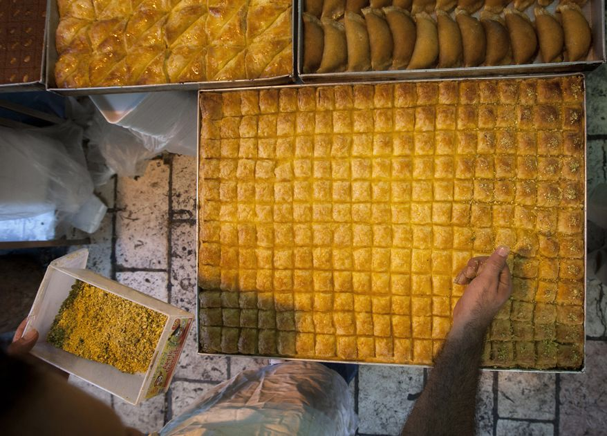 A Palestinian man prepares traditional Arab pastries Aug. 6, 2012, during the Muslim holy month of Ramadan in Jerusalem's Old City. Alongside hundreds of millions of Muslims observing the sunrise-to-sundown fast of Ramadan, a defiant minority goes underground each year during the holy month, scarfing down sandwiches and sneaking cigarettes when no one is looking. (Associated Press)