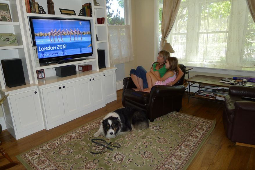 Julie O'Grady watches the 2012 Olympics on Aug. 9, 2012, with her daughter Molly and dog Bosco in her home in Palo Alto, Calif. (Associated Press)