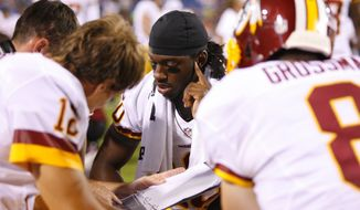 Washington Redskins quarterback Robert Griffin III (center) goes over plays with other quarterbacks during the second half of the Redskins' 7-6 preseason win over the Buffalo Bills in Orchard Park, N.Y., on Thursday, Aug. 9, 2012. (Associated Press)