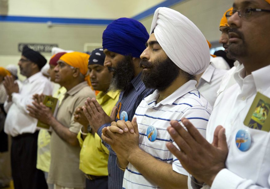 ** FILE ** Mourners attend the funeral and memorial service for the six victims of the Sikh temple of Wisconsin mass shooting in Oak Creek, Wis., on Aug. 10, 2012. (Associated Press)