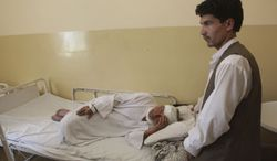 ** FILE ** An Afghan man who was wounded in a suicide attack lies in a hospital in Samangan province north of Kabul Afghanistan, Saturday, July, 14, 2012. (AP Photo/Jawed Dehsabzi)