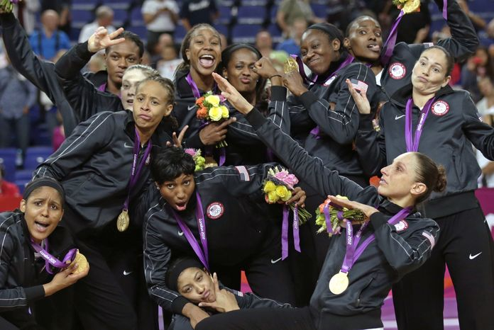 The United States' basketball team pose with their gold medals at center court after beating France during the women's gold medal basketball game at the 2012 Summer Olympics, Saturday, Aug. 11, 2012, in London. (AP Photo/Charles Krupa)