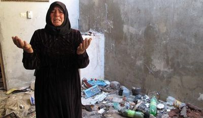 In this photo from Sunday, Aug. 5, 2012, Fatoum Obeid, 50, stands in a pile of trash left by Syrian soldiers who occupied her home in Atarib, Syria. In recent months, rebels have seized a huge swath of territory in northern Syria, giving them a freedom to move and organize unprecedented in the 17-month conflict. (AP Photo/Ben Hubbard)