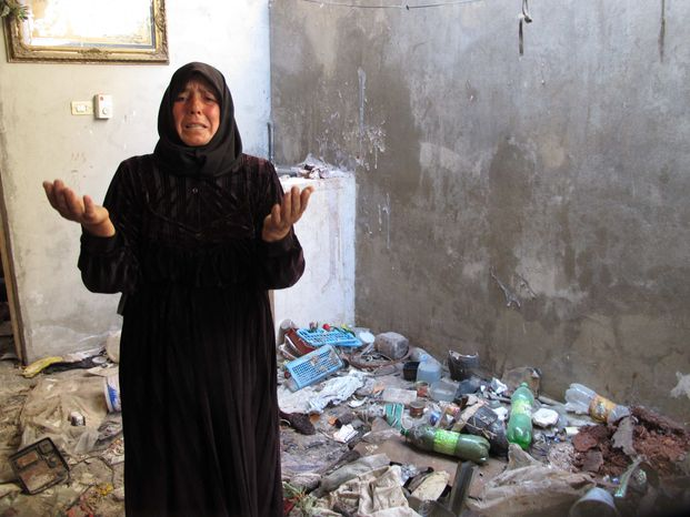 In this photo from Sunday, Aug. 5, 2012, Fatoum Obeid, 50, stands in a pile of trash left by Syrian soldiers who occupied her home in Atarib, Syria. In recent months, rebels have seized a huge swath of territory in northern Syria, giving them a freedom to move