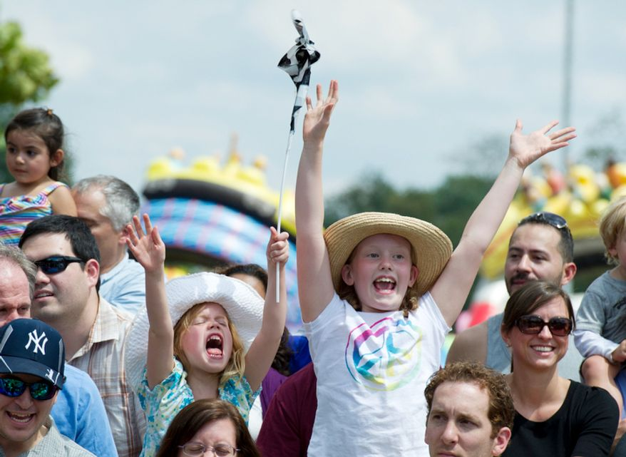 Sister Ellie (left), 6 and Hannah Holmes, 8, both from Arlington, raise their hands as they try to get selected to help out with the Sue Wee Flying Piglet Races at the Arlington County Fair. (Barbara L. Salisbury/The Washington Times)