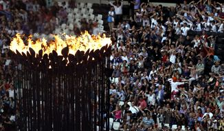 The Olympic flame burns as spectators gather in Olympic Stadium to attend the closing ceremony of the 2012 Summer Olympics on Sunday, Aug. 12, 2012, in London. (AP Photo/Hassan Ammar)