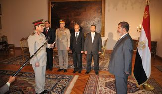 Egyptian President Mohammed Morsi (right) swears in the newly-appointed defense minister, Lt. Gen. Abdel-Fattah el-Sissi, in Cairo on Sunday, Aug. 12, 2012. (AP Photo/Egyptian Presidency)
