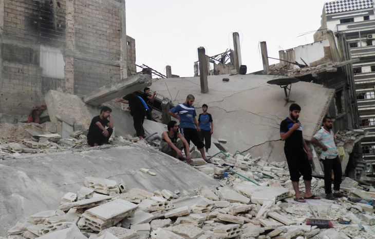 This citizen journalism image provided by Shaam News Network and taken on Saturday, Aug. 11, 2012, purports to show Syrians standing in the rubble of a destroyed building from shelling by Syrian forces in the Khaldiyeh neighborhood of Syria's Homs province. (AP Photo/Shaam News Network)