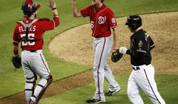 Washington Nationals catcher Jesus Flores high-fives teammate Tyler Clippard as Arizona Diamondbacks' Paul Goldschmidt heads to the dugout after making the final out  of a baseball game, Saturday, Aug. 11, 2012, in Phoenix. The Nationals won 6-5. (AP Photo/Matt York)