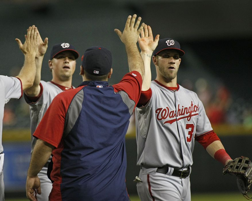 Washington Nationals' Bryce Harper, right, and his fellow teamates are congratulated by the coaching staff following their 9-1 victory over the Arizona Diamondbacks during a baseball game on Friday, Aug. 10, 2012, in Phoenix. (AP Photo/Ralph Freso)