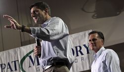 Republican presidential candidate Mitt Romney (right) listens as his vice presidential running mate, Rep. Paul Ryan, speaks during a campaign stop at the NASCAR Technical Institute on Sunday, Aug. 12, 2012, in Mooresville, N.C. (AP Photo/Mary Altaffer)