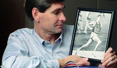 At his home in Lawrence, Kan., in 1991, former Olympian Jim Ryun takes a look at a photograph taken of him at the Olympics in Mexico City in 1968, where he won a silver medal in the 1,500-meter run. (Associated Press)