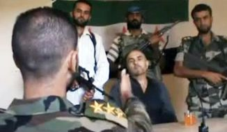 This image purports to show Col. Rafik Mohammed Suleiman, a Syrian pilot, being interrogated by a rebel officer after his Soviet-made MiG warplane was apparently hit by ground fire over Deir el-Zour province in Syria on Monday. (Associated Press)