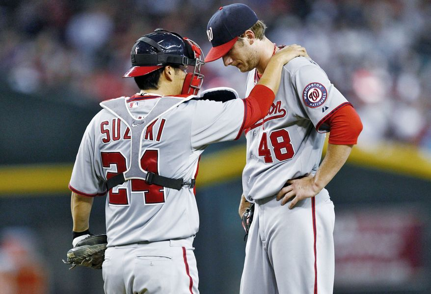 Everything is new for Washington catcher Kurt Suzuki, particularly the pitchers (shown with Ross Detwiler). (Associated Press)