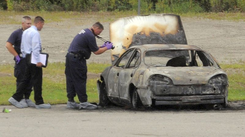 Police investigate a vehicle that burned before dawn on Aug. 13, 2012, off Target Industrial Circle in Bangor, Maine. After the fire was extinguished, three bo