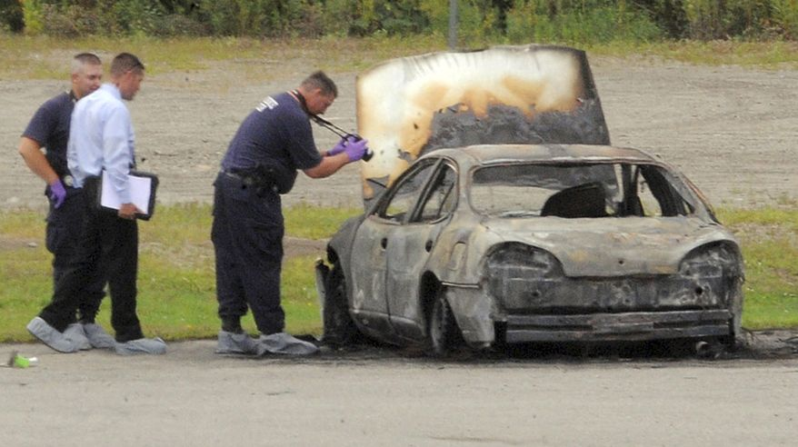 Police investigate a vehicle that burned before dawn on Aug. 13, 2012, off Target Industrial Circle in Bangor, Maine. After the fire was extinguished, three bodies were found inside the parked car. (Associated Press/Bangor Daily News, Gabor Degre)