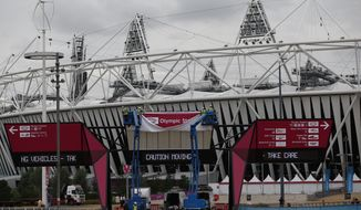Workers adjust a sign outside the Olympic Stadium in London on Monday, Aug. 13, 2012, to prepare for the upcoming Paralympic Games. (AP Photo/Matt Dunham)