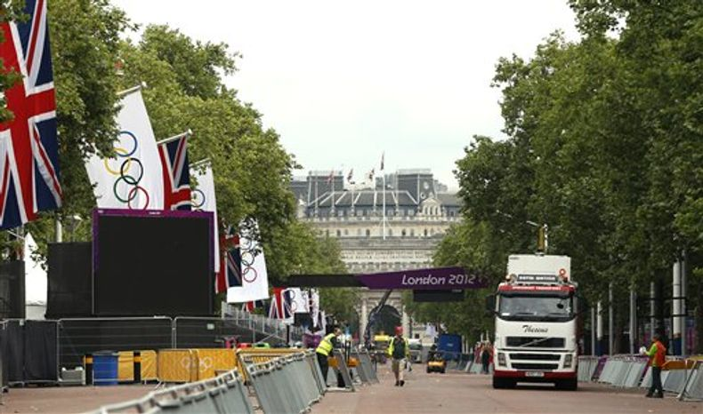 Workmen start dismantling the finish to the Olympic marathon course in the Mall near Buckingham Palace, not pictured, in London, Monday Aug. 13, 2012, following the closing ceremony of the 2012 Summer Olympics. The London summer games ended late Sunday, with the next summer games scheduled to be in Rio de Janeiro, Brazil, in 2016. (AP Photo/Alastair Grant)