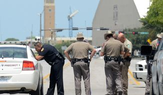 Texas State troopers and Brazos Valley lawmen work the scene of a Aug. 13, 2012, shooting of two fellow law officers in College Station, Texas. Police said at least one law enforcement officer and one civilian were killed in the shooting near Texas A&M University's campus. (Associated Press/College Station Eagle)