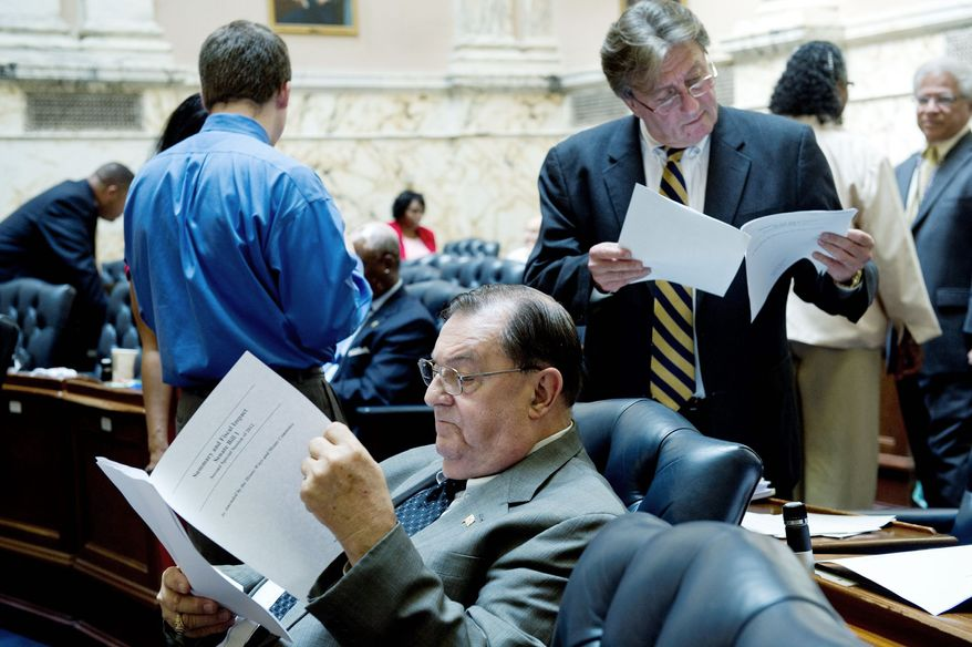 Delegates Norman Conway (left) and Luiz Simmons read through a summary and financial analysis as they wait for the debate on the gambling bill to begin at the State House in Annapolis. There were 39 amendments to be considered. The legislative session extended into the night Tuesday. (Barbara L. Salisbury/The Washington Times)