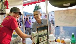 President Obama visits Cookie Smith at the CinnieSmiths cinnamon miniroll stand at the Iowa State Fair Monday in Des Moines during a three-day state tour. (Associated Press)