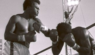 ** FILE ** This May 20, 1983 file photo shows Michael Dokes, left, battling Mike Weaver in a World Boxing Association heavyweight title fight in Las Vegas. The Rhoden Memorial Home in Akron, Ohio, said Dokes died Saturday, Aug. 11, 2012. The Akron Beacon Journal reported that the boxer died in an Akron hospice from liver cancer. He was 54. (AP Photo/File)