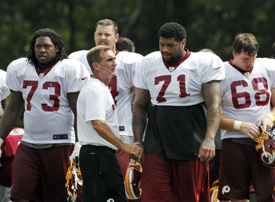 ** FILE ** Washington Redskins coach Mike Shanahan talks with offensive tackle Trent Williams (71) after practice at the team's NFL football training camp at Redskins Park on Tuesday, Aug. 14, 2012, in Ashburn, Va. (AP Photo/Alex Brandon)
