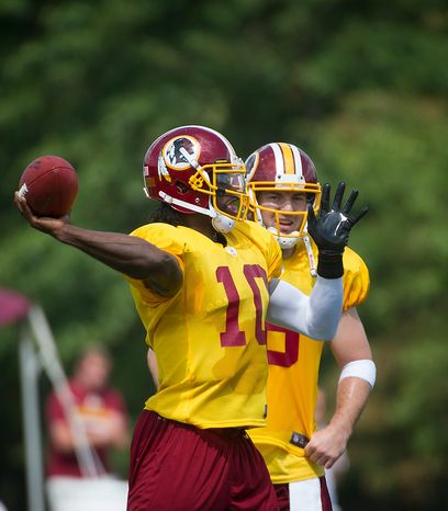 With Rex Grossman (right) looking on Robert Griffin III makes a pass during the Redskins training camp at Redskins Park in Ashburn, Va., Monday, August 13, 2012.  (Rod Lamkey Jr./The Washington Times)
