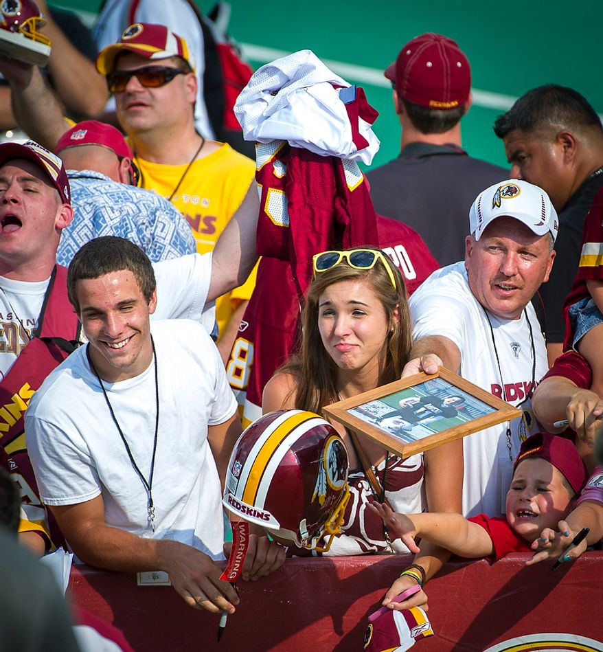 Fans crowd the sideline for a chance for an autograph by Redskins quarterback Robert Griffin III following the Redskins training camp at Redskins Park in Ashburn, Va., Monday, August 13, 2012. (Rod Lamkey Jr./The Washington Times)