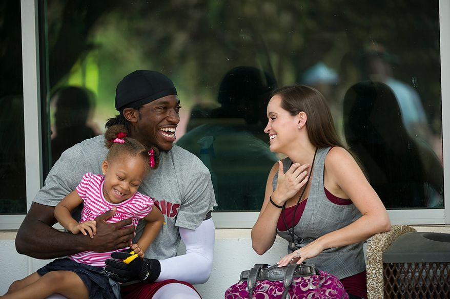 Redskins quarterback robert Griffin III plays with Trinity Austin, 3, as he joined by his fiancee Rebecca Liddicoat (right) following the Redskins training camp at Redskins Park in Ashburn, Va., Monday, August 13, 2012.  (Rod Lamkey Jr./The Washington Times)