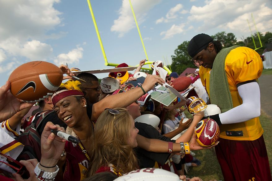 Fans line up and cram into each other, reaching and screaming out with their souvenirs to be signed by Redskins quarterback Robert Griffin III (right) following the Redskins training camp at Redskins Park in Ashburn, Va., Monday, August 13, 2012.  (Rod Lamkey Jr./The Washington Times)