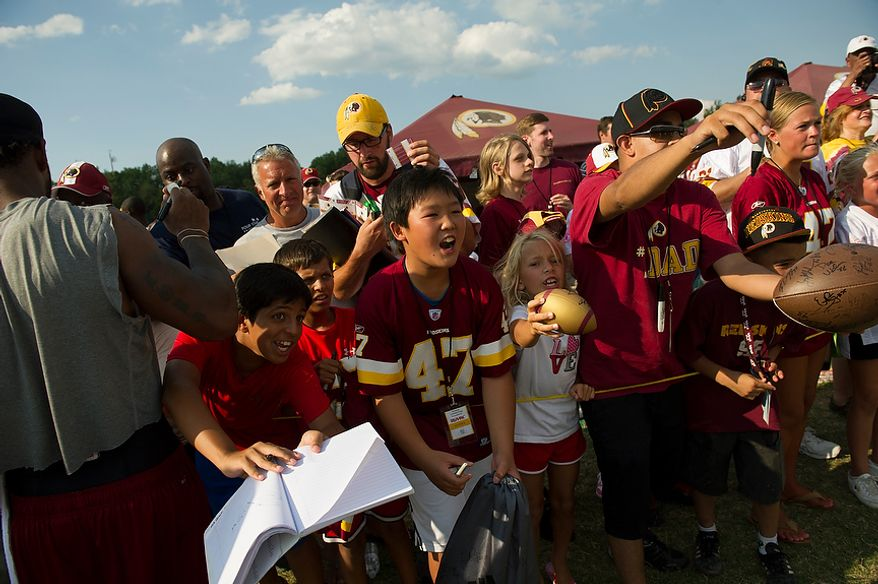 Fans line up and cram into each other, reaching and screaming out with their souvenirs to be signed as Redskins quarterback Robert Griffin III makes his way to the locker room following the Redskins training camp at Redskins Park in Ashburn, Va., Monday, August 13, 2012.  (Rod Lamkey Jr./The Washington Times)