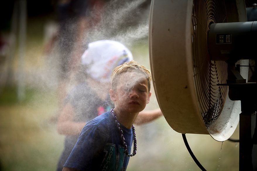 Adam Hopkins, 9, of Ashburn, Va., cools from the misting fan during the Redskins training camp at Redskins Park in Ashburn, Va., Tuesday, August 14, 2012. This is the last day that fans will be able to watch their team practice in this area. Next year the Redskins will move their practice facility to the Richmond, Va., area. (Rod Lamkey Jr./The Washington Times)