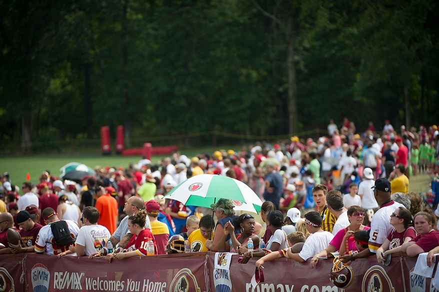 Throngs of people gather along the sideline for a glimpse of the action during the Redskins training camp at Redskins Park in Ashburn, Va., Tuesday, August 14, 2012. This is the last day that fans will be able to watch their team practice in this area. Next year the Redskins will move their practice facility to the Richmond, Va., area. (Rod Lamkey Jr./The Washington Times)