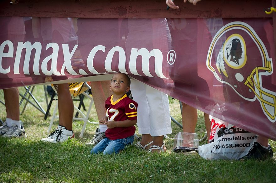 Ralph Featherstone, 3, of Quantico, Va., watches the action on the field from under the banner during Redskins training camp at Redskins Park in Ashburn, Va., Tuesday, August 14, 2012. This is the last day that fans will be able to watch their team practice in this area. Next year the Redskins will move their practice facility to the Richmond, Va., area. (Rod Lamkey Jr./The Washington Times)
