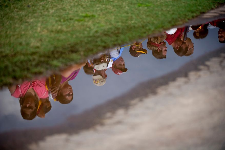 Fans are seen reflected in a puddle as they wait for players to offer autographs following Redskins training camp at Redskins Park in Ashburn, Va., Tuesday, August 14, 2012. This is the last day that fans will be able to watch their team practice in this area. Next year the Redskins will move their practice facility to the Richmond, Va., area. (Rod Lamkey Jr./The Washington Times)