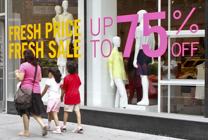 **FILE** Shoppers in New York pass signs for discounted clothing sales on July 19, 2012. (Associated Press)
