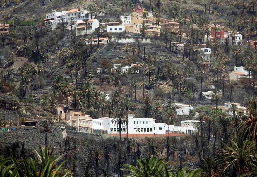 Houses stand in a burned valley in Barranco de Guada on the Canary island of La Gomera, Spain, on Tuesday. Morocco sent two water-carrying planes to help Spanish firefighters in the battle to extinguish persistent wildfires. Cooler temperatures and a wind shift are helping turn the tide. (Associated Press)