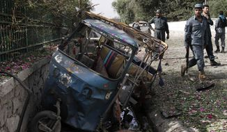 Afghan police inspect the scene after a bombing in Jalalabad, Afghanistan, on Monday, Aug. 13, 2012. At least five civilians were injured as a bomb targeting the government-employee vehice went off, a police source said. (AP Photo/Rahmat Gul)