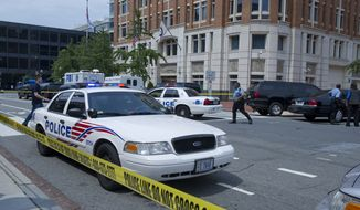 FBI and Metropolitan Police Department officials surround the Family Research Council building at 8th and G streets N.W. in Washington, D.C. on Wednesday, Aug. 15, 2012 following the shooting of a security guard at the conservative Christian lobbying group. The security guard was evidently shot in the arm before he wrestled the gunman to the ground. The suspect has now been taken into custody. (Barbara L. Salisbury/The Washington Times)