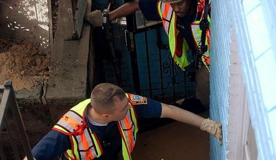 ** FILE ** D.C. firefighters (from top) Lt. Brian Alston, Ryan Doyle, Greg Smith and Shawn Welch attempt to drain the entrance area of a flooded residence in the Adams Morgan area in this 2009 file photo.