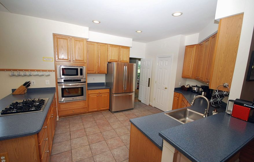 The kitchen features ceramic tile flooring, Corian counters, tall wood cabinets, stainless steel appliances and a center island.