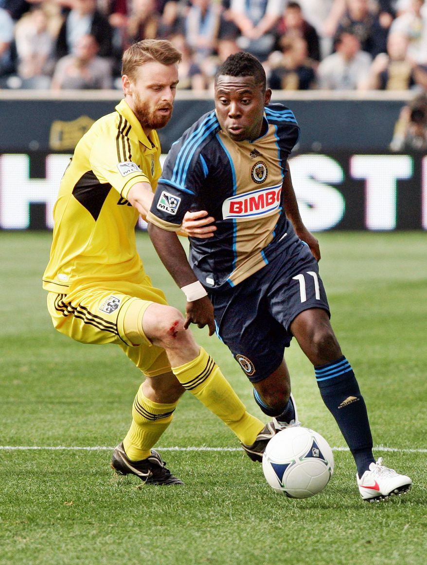 Columbus Crews' Eddie Gaven, left, reaches around Philadelphia Union's Freddy Adu as they chase the ball during the second half of an MLS soccer match, Saturday, April 14, 2012, in Chester, Pa. The Union won 1-0. (AP Photo/Tom Mihalek)